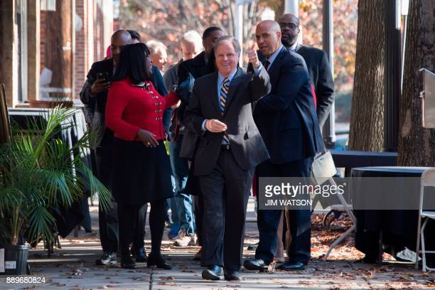 Democratic Senatorial candidate Doug Jones gives a thumbsup as he walks with US Congresswoman Terri Sewell and US Senator Cory Booker to campaign...
