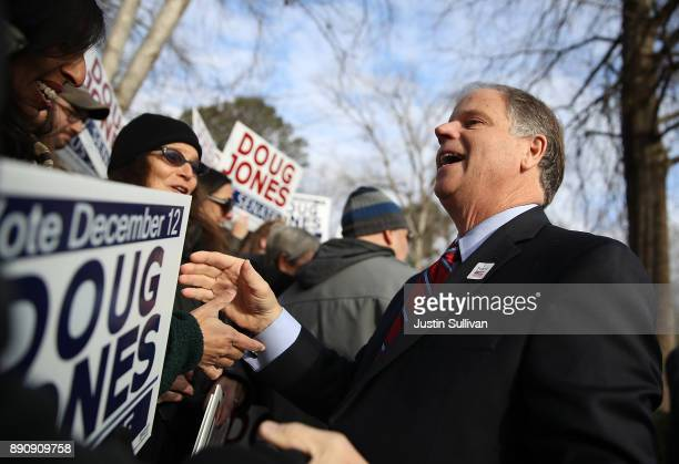 Democratic senatorial candidate Doug Jones greets supporters after voting at Brookwood Baptist Church on December 12 2017 in Mountain Brook Alabama...