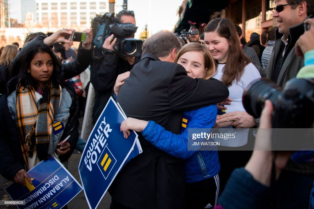 Democratic Senatorial candidate Doug Jones (C) hugs a supporter outside his campaign headquarters in Birmingham, Alabama, on December 10, 2017. /