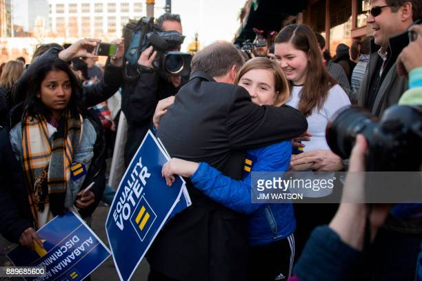 Democratic Senatorial candidate Doug Jones hugs a supporter outside his campaign headquarters in Birmingham Alabama on December 10 2017 / AFP PHOTO /...
