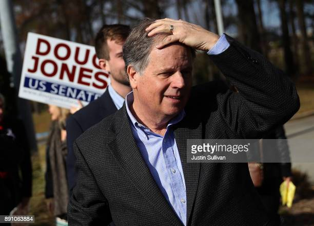 Democratic senatorial candidate Doug Jones prepares to greet voters outside of a polling station at the Bessemer Civic Center on December 12 2017 in...