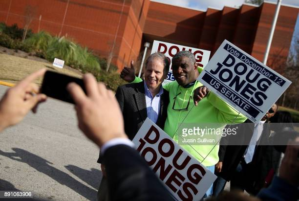 Democratic senatorial candidate Doug Jones takes a picture with voters outside of a polling station at the Bessemer Civic Center on December 12 2017...