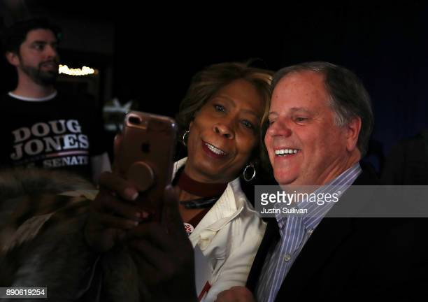 Democratic Senatorial candidate Doug Jones takes a selfie with a supporter during a get out the vote campaign rally on December 11 2017 in Birmingham...