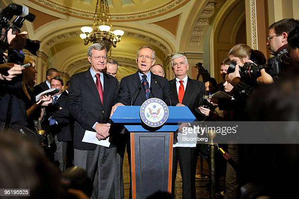 Democratic Senators Max Baucus of Montana left and Christopher Dodd of Connecticut right listen to Majority Leader Harry Reid of Nevada speak at a...