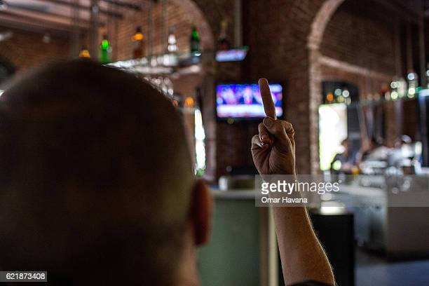 Democratic supporter reacts by giving th finger after Donald Trump's victory is announced on November 9 2016 in Phnom Penh Cambodia Dozens of...
