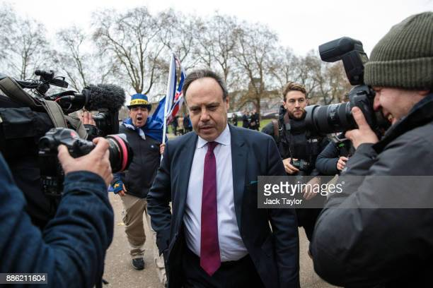 Democratic Unionist Party Deputy Leader Nigel Dodds leaves after speaking to members of the media as a protester holding flags shouts after him...