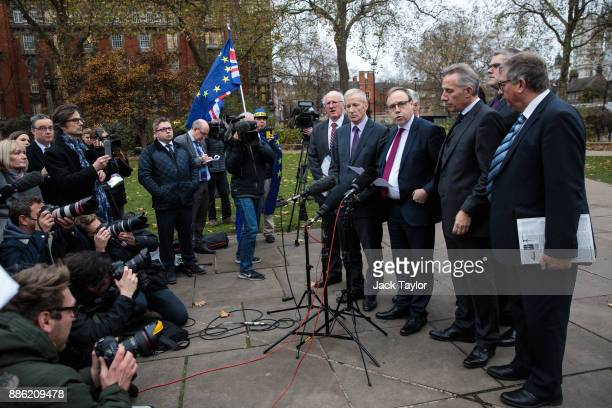 Democratic Unionist Party Deputy Leader Nigel Dodds speaks to members of the media as a protesters waves flags outside the Houses of Parliament on...