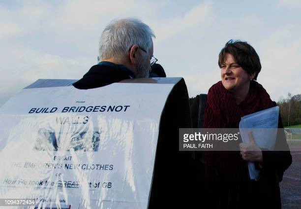 Democratic Unionist Party leader Arlene Foster greets a protester outside the Government Buildings on the Stormont Estate in Belfast Northern Ireland...