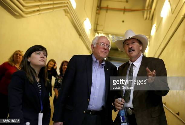 Democratic US Congressional candidate Rob Quist talks with US Sen Bernie Sanders before the start of a campaign rally at the University of Montana on...