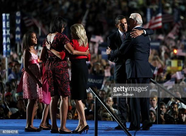 Democratic US Presidential nominee Sen Barack Obama speaks with running mate US Sen Joe Biden while Michelle Obama and Jill Biden hug and daughters...