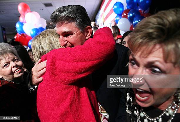 Democratic U.S. Senate candidate and West Virginia Governor Joe Manchin is hugged by a supporter as his wife Gayle celebrates during a election night...