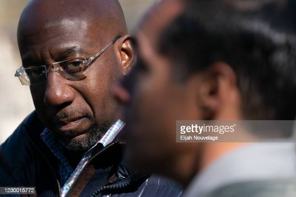 Democratic U.S. Senate candidate Raphael Warnock looks on as former Democratic presidential candidate Julián Castro speaks during a campaign event on...