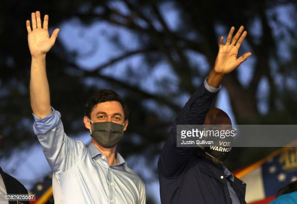 """Democratic U.S. Senate candidates Jon Ossoff and Rev. Raphael Warnock wave to supporters during a """"Get Out the Early Vote"""" drive-in campaign event on..."""