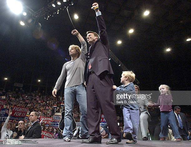 Democratic vice presidential candidate Sen John Edwards and musician Jon Bon Jovi wave to the crowd while Edward's son Jack clings to his pants leg...