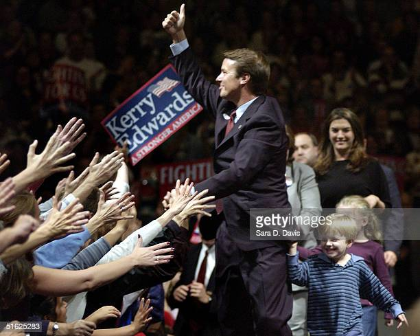 Democratic vice presidential candidate Sen John Edwards greets the crowd as son Jack clings to his coat before the A Fresh Start for America rally on...