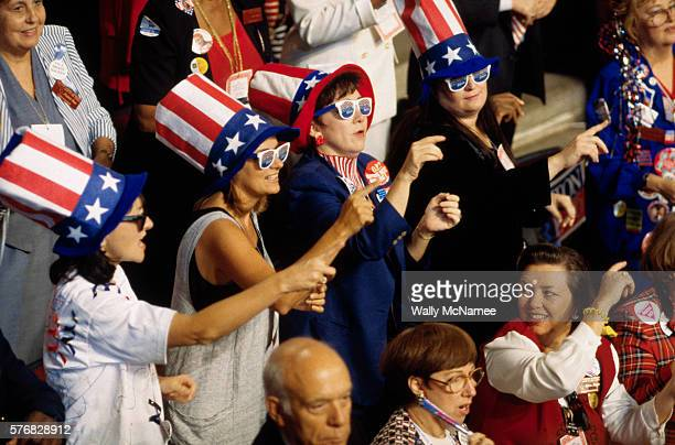 Democrats at a National Convention dance the Macarena in matching patriotic hats and sunglasses