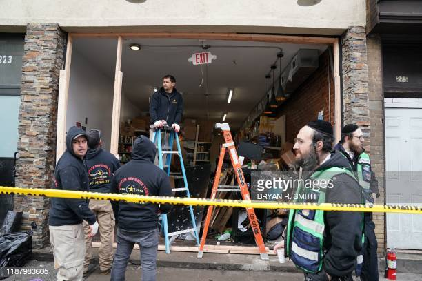 Demolition and recovery crews work at the scene of the December 10 2019 shooting at a Jewish Deli on December 11 2019 in Jersey City New Jersey The...