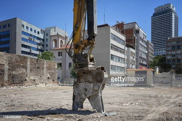 demolition arm at rest in a construction site on a sunny day. - emreturanphoto stock pictures, royalty-free photos & images