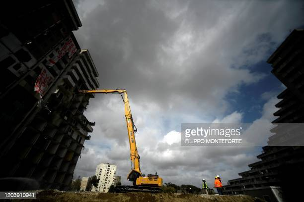 TOPSHOT A demolition crane destroys part of the buildings called le Vele in Scampia a modern suburb in the far north of Naples on February 26 2020...