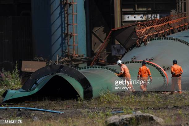 Demolition crews inspect the BOS plant chimney after it is brought down in a controlled demolition on the former SSI steel site on August 02, 2021 in...