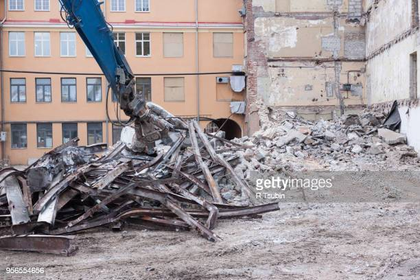 demolition truck in action. heap of rubble and a demolished building in the background - house collapsing stock pictures, royalty-free photos & images