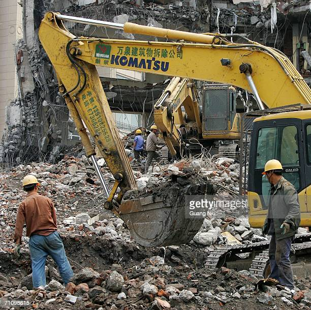 Demolition vehicles knock down an old building on June 1 2006 in Beijing China China has imposed an order preventing land being used for luxury...
