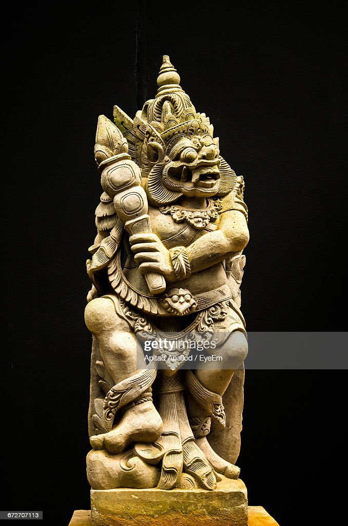 Demon Sculpture Against Black Background Stock Photo - Getty