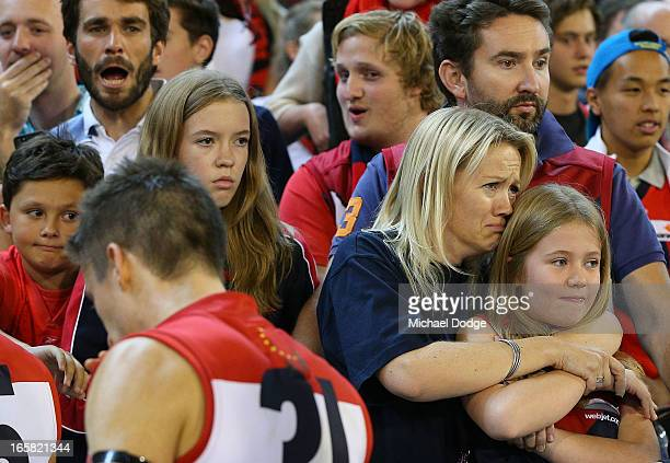 Demons fan cries after the game as Jack Grimes walks to the rooms after a big loss during the round two AFL match between the Essendon Bombers and...
