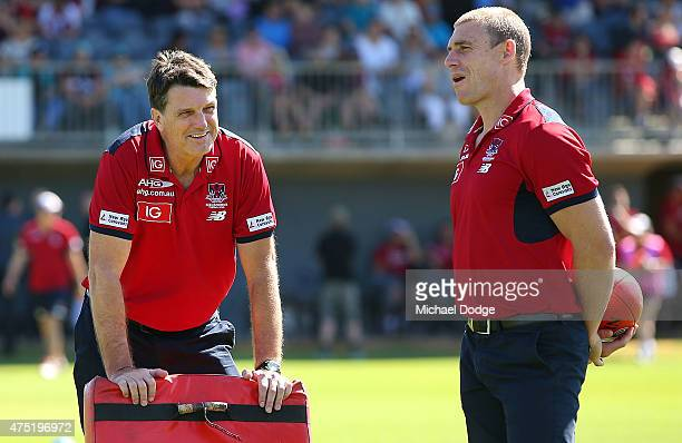 Demons head coach Paul Roos talks with assistant coach Simon Goodwin during the round nine AFL match between the Melbourne Demons and the Port...