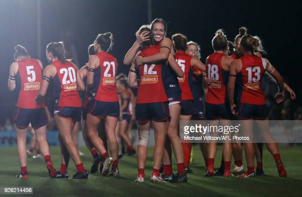 Demons players celebrate as the final siren sounds during the 2018 AFLW Round 05 match between the Melbourne Demons and the Brisbane Lions at Casey...