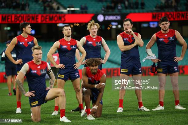 Demons players look dejected during the round 13 AFL match between the Melbourne Demons and the Collingwood Magpies at Sydney Cricket Ground on June...