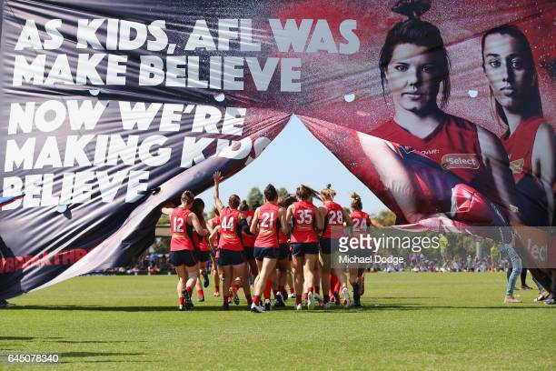 Demons players run through the banner during the round four Women's AFL match between the Melbourne Demons and the Carlton Blues at Casey Fields on...