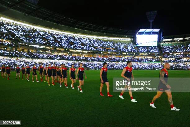 Demons players walk onto the field during the 2018 AFL round five match between the Melbourne Demons and the Richmond Tigers at the Melbourne Cricket...