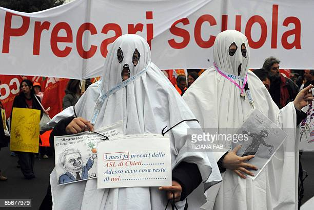 Demonstators dressed as ghosts march during a rally in Rome March 28 2009 Protesters threw red paint egg and smoke bombs at Romebased banks insurance...