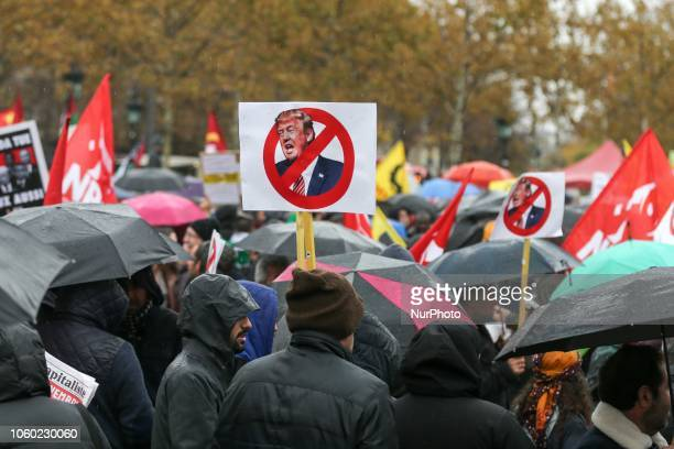 Demonstators holds signs against US president Donald Trump at the Place de la Republique in central Paris on November 11 as leaders from around the...