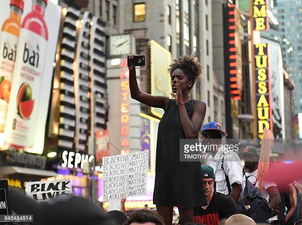 Demonstators rally in the middle of Times Square after they march through the city and call for justice for Alton Sterling and Philandro Castile on...