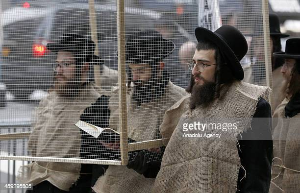 Demonstators stand in a mock prison during a protest in New York City on December 24 2013 Hundreds of Orthodox Jewish students marched to the Israeli...