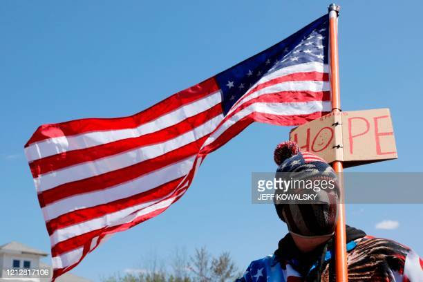 TOPSHOT demonstraA man holds a US flag outside the shop of Barber Karl Manke who faces two misdemeanor charges for reopening his business despite...
