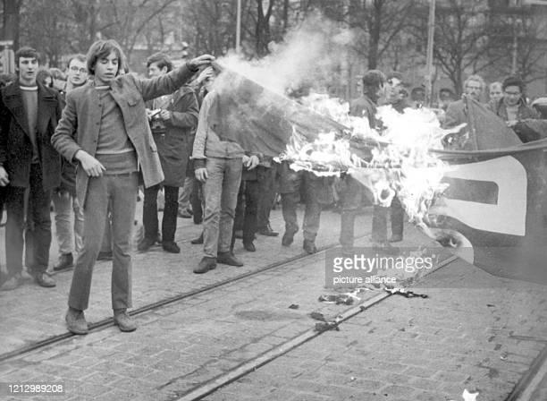 Demonstranten halten eine brennende SPD-Flagge, die von ihnen angezündet wurde, am Sonntag vor der Meistersingerhalle in Nürnberg in die Höhe. Mit...