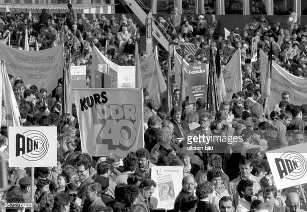 Demonstranten laufen mit Transparenten mit der Aufschrift 'Kurs DDR 40' und anderen Losungen bei der Demonstration am 1 Mai 1989 in der...