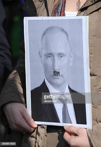 Demonstranten während Solidaritätsdemonstration in Berlin für Frieden und Demokratie in der Ukraine Putin mit Hitlerbärtchen auf einer Fotografie