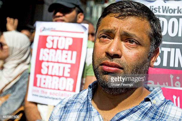 A demonstrater stands amongst others during a march and rally outside the Israeli Embassy to oppose Israel's actions in Gaza on July 19 2014 in...