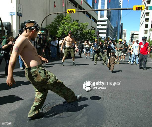 Demonstraters block an intersection during the morning rush hour as they play a game of soccer during a protest march June 26 2002 in downtown...