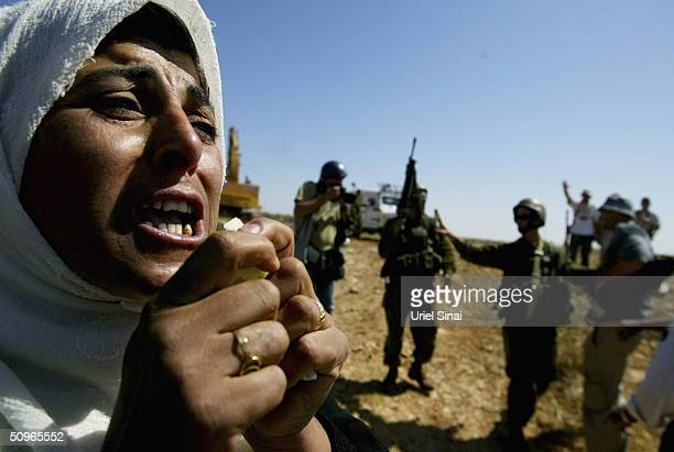 A demonstrating Palestinian villager weeps as Israeli soldiers block her way from the West Bank village of Iskaka June 16 2004 which lies to the...