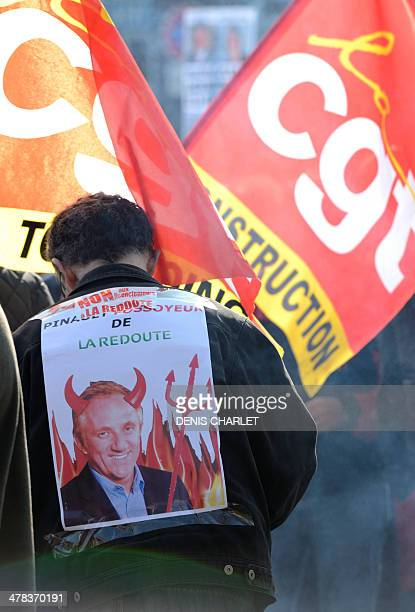 """Demonstrating worker wears a sign reading """"Pinault is killing La Redoute"""" as employees of French retail company 'La Redoute' take part in a protest..."""