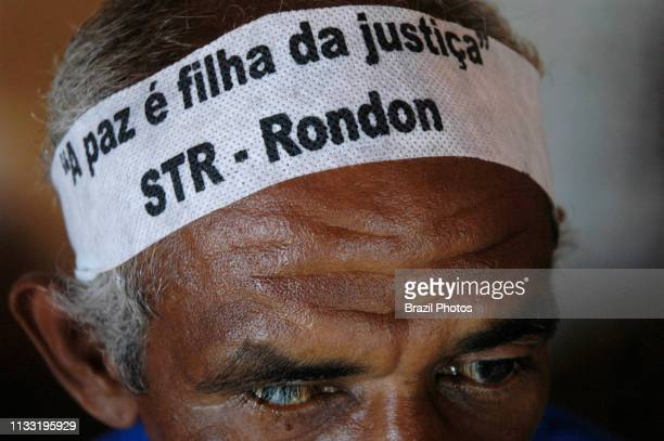 Demonstration for land reform in Amazon Brazil oneeye blind landless worker wears forehead strip saying A Paz é filha da Justiça STR Rondon