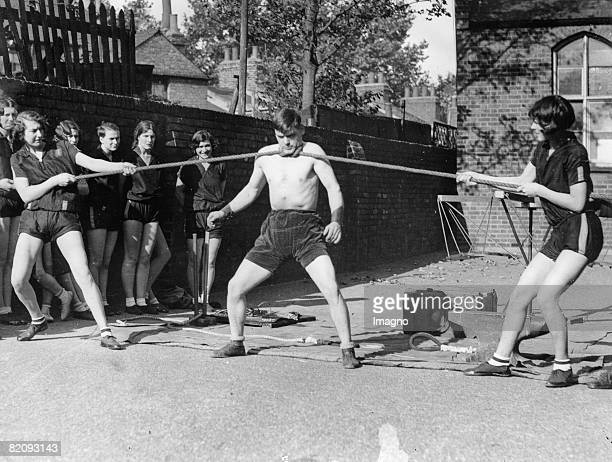 Demonstration of physical strength a coach with a rope round his neck which is pulled by his pupils Photograph England Around 1930 [Demonstration von...