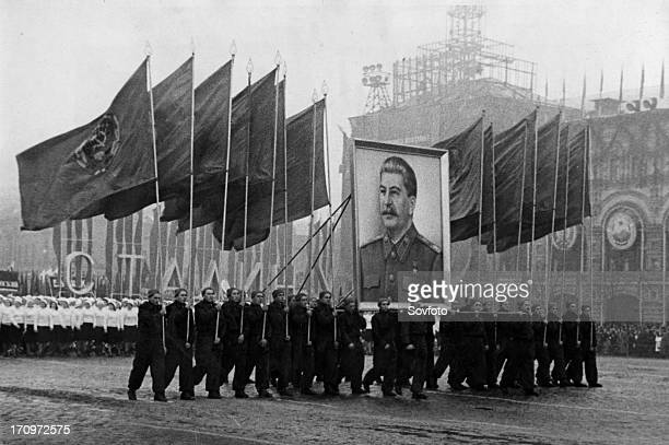A demonstration / parade of the working people in red square in moscow on november 7 the sportsmen are carrying soviet flags and an image of stalin