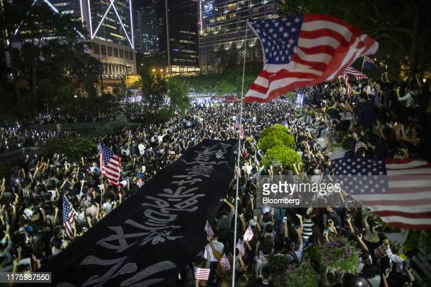 Demonstrations hold a banner and American flags during a rally in support of the Hong Kong Human Rights and Democracy Act in Hong Kong China on...