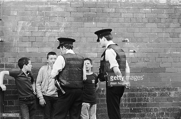 Demonstrations in the Protestant area of the city provoke unrest in Northern Ireland's capital RUC police officers talk to some children in the...